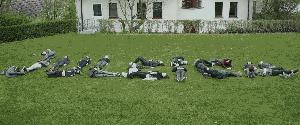 Jugendlich liegen auf der Wiese und bilden das Wort JULEICA nach.